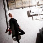 Foto aus einem Beauty Shooting on Location eines weiblichen Models mit blonden Haaren, in einem schwarzen Abendkleid, stehend vor einer weißen Brick Wall mit elektrischen Geräten