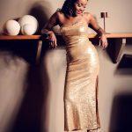 Foto aus einem Beauty Shooting eines weiblichen Models mit langen schwarzen Harren, in einem glitzernden, goldenen Abendkleid, stehend vor einer braunen Wand
