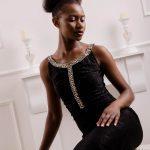 Foto aus einem Beauty Shooting eines weiblichen Models mit schwarzem Afro, in einem schwarzen Abendkleid, sitzend auf einer barocken Fotokulisse