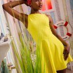 Foto aus einem Beauty Shooting eines weiblichen Models mit schwarzem Afro und Kopftuch, in einem gelben Sommerkleid, stehend in einer maritimen Fotokulisse