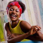 Foto aus einem Beauty Shooting eines weiblichen Models mit schwarzem Afro und Kopftuch, in einem gelben Sommerkleid, sitzend in einer maritimen Fotokulisse