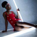 Foto aus einem Beauty Shooting eines weiblichen Models mit schwarzem Afro und Kopftuch, in einem roten Kleid, auf dem Boden sitzend vor einer grauen Wand