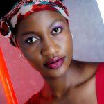 Foto aus einem Beauty Shooting eines weiblichen Models mit schwarzem Afro und Kopftuch, in einem roten Kleid, stehend vor einer grauen Wand