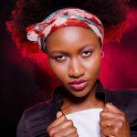 Foto aus einem Beauty Shooting eines weiblichen Models mit schwarzem Afro, in einem legeren Outfit mit Top, schwarzer Jacke und Kopfband, stehend vor schwarzem Hintergrund
