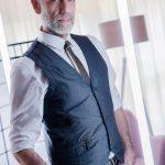 Portraitfotos eines männlichen Models mit Glatze und Bart, in einem Retro Outfit mit karierten Hosen, Weste, Krawatte und Schiebermütze, stehend in einer Retro Kulisse