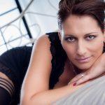 Erotikfoto eines weiblichen Models mit gebundenen, braunen Haaren, in schwarzen Dessous, liegend auf einem Bett