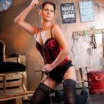 Erotikfoto eines weiblichen Models mit gebundenen, braunen Haaren, in roten Dessous, kniend in einer Vintage Fotokulisse