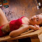 Foto aus einem Erotik Shooting eines weiblichen Models mit kurzen blonden Haaren, in roten Dessous, liegend in einer Vintage Fotokulisse