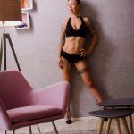 Foto aus einem Erotik Shooting eines weiblichen Models in schwarzen Dessous mit kurzen blonden Haaren, stehend in einer Retro Fotokulisse