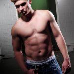 Portraitfoto eines männlichen Models mit freiem Oberkörper und Jeans, stehend vor einer weißen Brick Wall mit grüner Tür